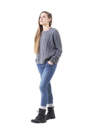 Casual giovane donna carina che indossa jeans e maglione grigio camminando e alzando lo sguardo stupito. Corpo pieno isolato su sfondo bianco.