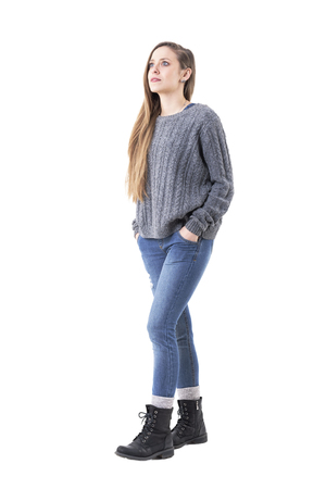 Casual young cute woman wearing jeans and gray sweater walking and looking up amazed. Full body isolated on white background.