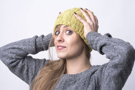 Portrait of cute young confident girl trying on yellow knitted cap for cold winter weather on light gray background. Stock Photo