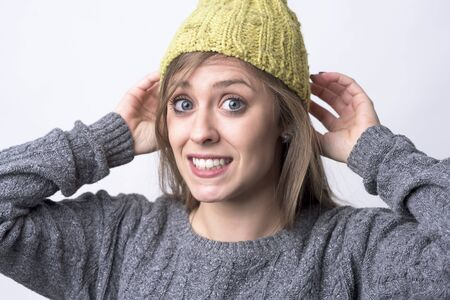 Playful funky expressive woman with yellow cap and cheesy grin smile at camera on light gray background. Stock Photo