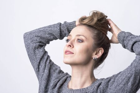 Portrait of independent beautiful young woman making hair bun hairdo herself on light gray background.