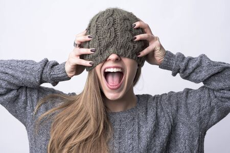 Conceptual portrait of young woman screaming with cap over her eyes and hands on head on light gray background.