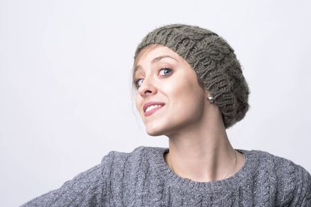 Portrait of confident charming young hipster woman with knitted cap posing and smiling on light gray background with copyspace.