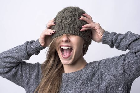Portrait of screaming young woman with knitted cap covering her eyes on light gray background.