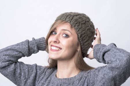 Cute charming young woman trying on gray knitted beanie cap smiling at camera on light gray background.