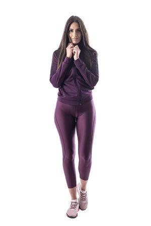 Basculador de mujer en forma deportiva en chándal morado posando y desnudándose mirando a la cámara. Cuerpo completo aislado sobre fondo blanco. Foto de archivo