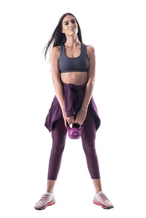 Front view of confident sportswoman athlete with kettlebell looking at camera. Full body isolated on white background.