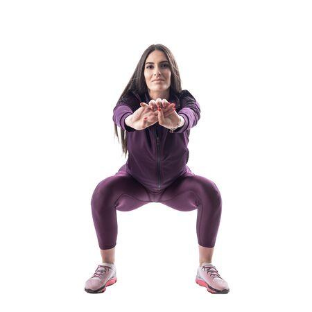 Vorderansicht eines attraktiven Aerobic- oder Fitnesstrainers, der Kniebeugenübungen macht. Ganzkörper isoliert auf weißem Hintergrund. Standard-Bild