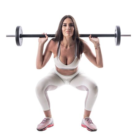 Low position of squat exercise with barbell done by athletic young woman fitness model. Full body isolated on white background.