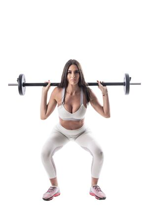 Mid position of squatting exercise with barbell done by attractive young fitness woman. Full body isolated on white background.