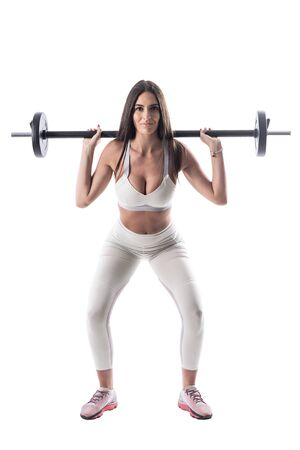 Young attractive brunette fitness woman doing barbell squat exercise. Full body isolated on white background.