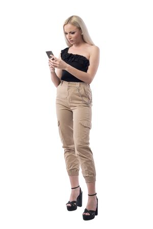 Angry frustrated stylish blonde woman reading and using mobile phone. Full body isolated on white background.