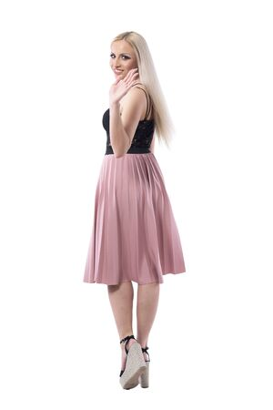 Back view of young blonde stylish woman in skirt walking away turning and waving hand goodbye to camera. Full body isolated on white background.