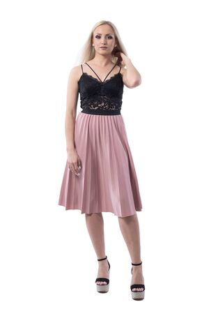 Confident young stylish blonde woman in summer skirt and lace top touching hair looking at camera. Full body isolated on white background.