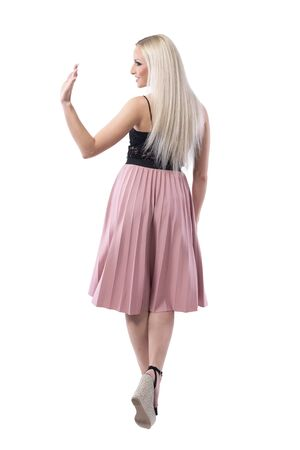 Back view of elegant stylish blonde woman walking away looking at someone and waving hand. Full body isolated on white background. Stock Photo