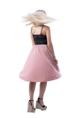 Back view of blonde young woman in summer skirt spinning and dancing with flying hair. Full body isolated on white background.