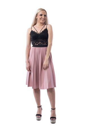 Cheerful young blonde woman in salmon color pleated skirt and lace top looking away. Full body isolated on white background. Фото со стока