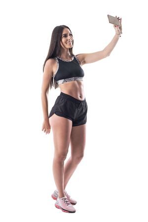 Happy relaxed woman fitness model taking selfie showing perfect abs muscles. Full body isolated on white background.