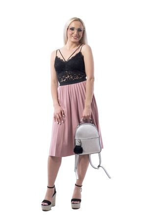 Happy smiling blond woman holding trendy faux leather gray shiny bag looking at camera. Full body isolated on white background. Stockfoto - 131810481