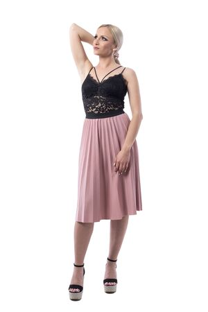 Elegant feminine gorgeous blonde fashion girl holding hair with hand looking up. Full body isolated on white background.