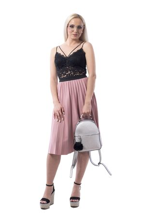 Confident young blond woman in modern fashion style carrying gray trendy bag. Full body isolated on white background.