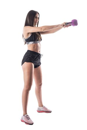 Side view dynamic action shot of attractive brunette fitness girl doing kettlebell swing exercises. Full body isolated on white background. Stockfoto - 131810389
