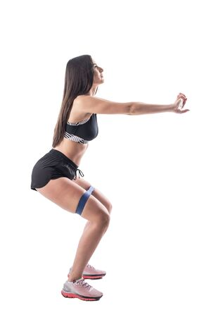 Side view of fitness sports woman doing squats with resistance bands on legs. Full body isolated on white background. Banco de Imagens