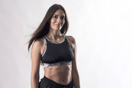 Portrait of attractive sporty athletic woman in black top with great abs smiling at camera on white background. Banco de Imagens