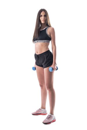 Side view of sporty gym young woman with dumbbells looking at camera. Full body isolated on white background. Foto de archivo