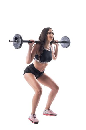Side view of attractive athletic gym woman doing squat exercises with barbell. Full body isolated on white background.
