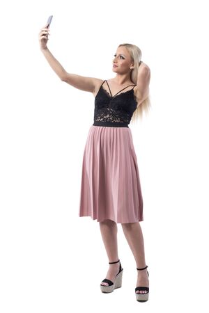 Young blonde influencer girl in stylish elegant classy fashion taking selfie holding hair. Full body isolated on white background.