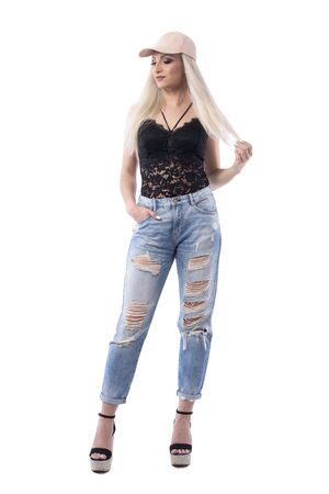 Cocky cool young funky woman in trendy clothes looking down smiling and touching hair. Full body isolated on white background. Stockfoto - 133451251