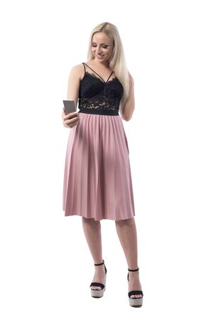 Confident happy young blonde woman in black lace top and skirt taking selfie with smart phone. Full body isolated on white background.