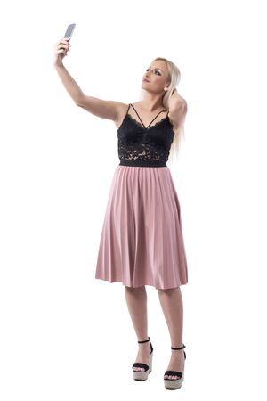 Elegant feminine young modern woman posing for selfie with smart phone. Full body isolated on white background. Stockfoto