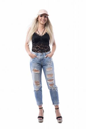 Happy carefree young cool trendy blonde girl in stylish clothes with hands in pockets looking away. Full body isolated on white background.