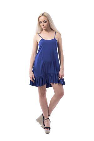 Mujer rubia joven emocional delicada en vestido de verano o camisón mirando hacia abajo seriamente. Cuerpo completo aislado sobre fondo blanco.