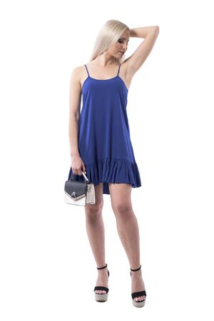 Blonde woman beauty in dress showing armpit soft skin posing with purse. Full body isolated on white background.