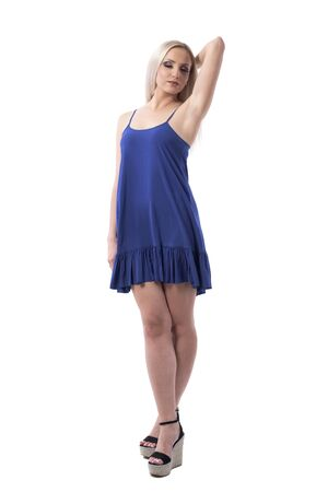 Elegant attractive blond woman in blue airy nightie posing with closed eyes and hand raised behind head. Full body isolated on white background. Stock fotó