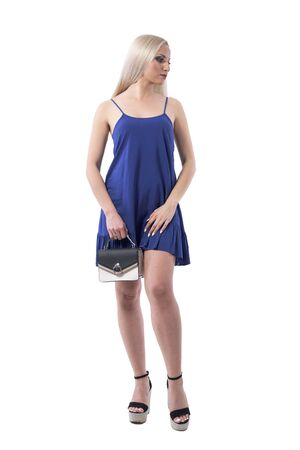 Serious modern stylish summer blonde girl in dress with purse posing and looking away. Full body isolated on white background.