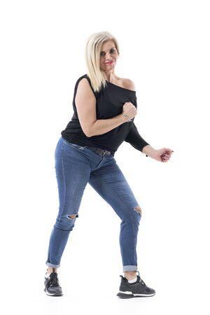 Mujer atractiva de mediana edad activa enérgica vital bailando sin preocupaciones en ropa casual. Longitud de cuerpo completo aislado sobre fondo blanco.