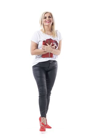 Happy playful energetic middle age woman smiling excited holding red bag in stylish clothes. Full body length isolated on white background.