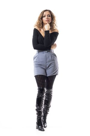 Confident fashion model girl with curly hair in black boots posing with hand on chin. Full body length isolated on white background.