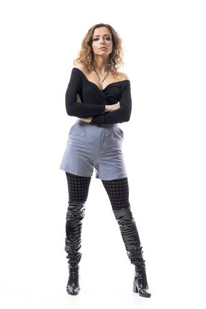 Cocky attitude brunette curly hair fashionable woman with crossed hands looking at camera. Full body length isolated on white background. Stockfoto