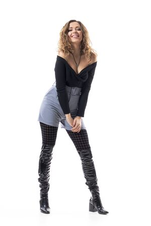 Cool modern fashionable young woman with curly hair posing in black leather knee-high boots. Full body length isolated on white background.