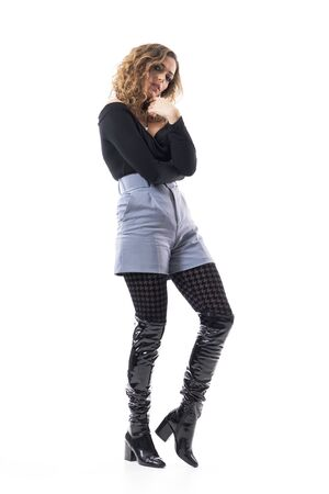 Side view of tender beautiful curly hair young woman wearing tights and knee high boots posing. Full body length isolated on white background. Stockfoto
