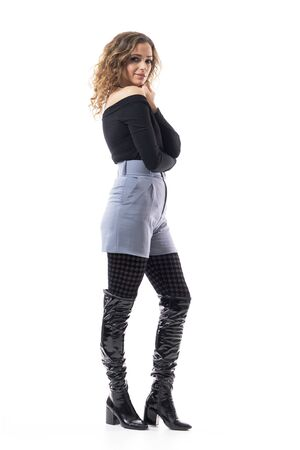 Profile view of delicate feminine stylish elegant young woman wearing patterned tights and boots. Full body length isolated on white background.
