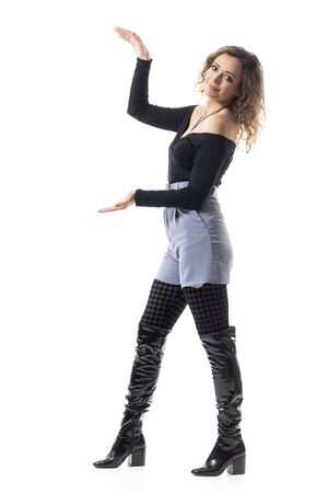 Happy young pretty woman in trendy clothes showing copy space with open arms. Full body isolated on white background.