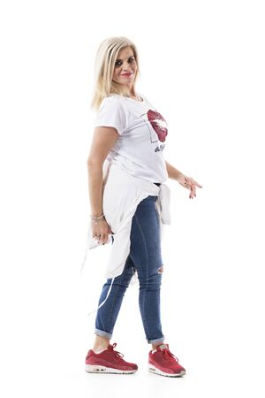 Cool stylish middle age blond hair woman walking and smiling at camera wearing jeans. Full body isolated on white background.  Archivio Fotografico