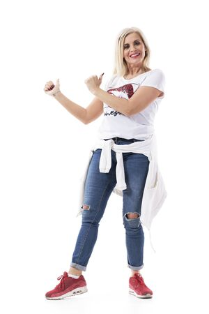 Cheerful excited middle age pretty woman showing thumbs up and looking at camera. Full body isolated on white background.