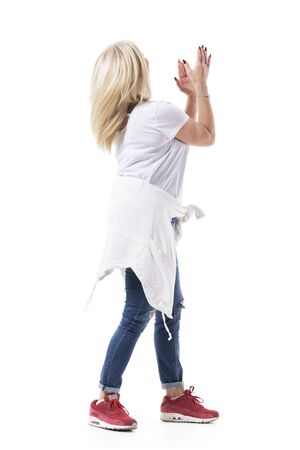 Back view of blonde unrecognizable mid age woman clapping hands applauding and showing support. Full body isolated on white background.